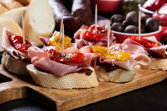 Spanish tapas with slices jamon serrano and grilled pepper. Also olives, salami, pickled onions, and peppers stuffed with cheese. Spanish cuisine royalty free stock image