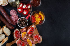 Spanish tapas with slices jamon serrano and grilled pepper. Also. Olives, salami, pickled onions, and peppers stuffed with cheese. Spanish cuisine. Top view stock photography