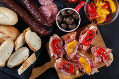 Spanish tapas with slices jamon serrano and grilled pepper. Also. Olives, salami, pickled onions, and peppers stuffed with cheese. Spanish cuisine. Top view stock image