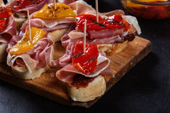 Spanish tapas with slices jamon serrano and grilled pepper. Also olives, salami, pickled onions, and peppers stuffed with cheese. Spanish cuisine royalty free stock photo