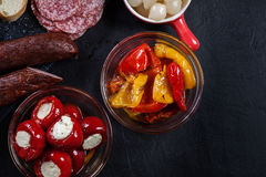 Spanish tapas with slices jamon serrano and grilled pepper. Also. Olives, salami, pickled onions, and peppers stuffed with cheese. Spanish cuisine. Top view royalty free stock image