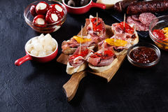 Spanish tapas with slices jamon serrano and grilled pepper. Also olives, salami, pickled onions, and peppers stuffed with cheese. Spanish cuisine stock images
