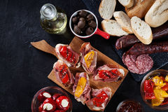 Spanish tapas with slices jamon serrano and grilled pepper. Also. Olives, salami, pickled onions, and peppers stuffed with cheese. Spanish cuisine. Top view stock photos