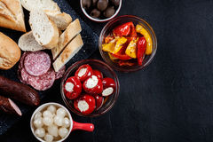 Spanish tapas with slices jamon serrano and grilled pepper. Also. Olives, salami, pickled onions, and peppers stuffed with cheese. Spanish cuisine. Top view royalty free stock photos