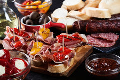Spanish tapas with slices jamon serrano and grilled pepper. Also olives, salami, pickled onions, and peppers stuffed with cheese. Spanish cuisine stock photos