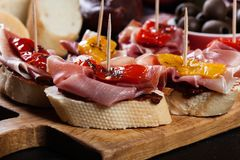 Spanish tapas with slices jamon serrano and grilled pepper. Also olives, salami, pickled onions, and peppers stuffed with cheese. Spanish cuisine stock image