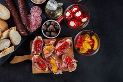 Spanish tapas with slices jamon serrano and grilled pepper. Also. Olives, salami, pickled onions, and peppers stuffed with cheese. Spanish cuisine. Top view royalty free stock images