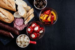 Spanish tapas with slices jamon serrano and grilled pepper. Also. Olives, salami, pickled onions, and peppers stuffed with cheese. Spanish cuisine. Top view stock images