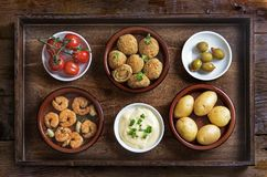 Spanish tapas such as baked olives, prawn shrimps, potatoes, tom Royalty Free Stock Images