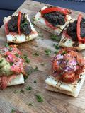 Spanish tapas on a wooden plate. Tapas served on bread stock image