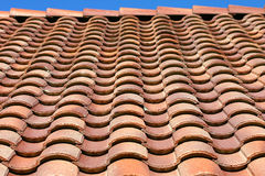 Spanish Tile Roof Texture. Waves of Spanish tile and a bit of blue sky Stock Images