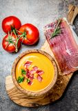 Spanish tomato soup Salmorejo served in olive wooden bowl with ham jamon serrano on stone background. Top view Stock Images