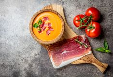 Spanish tomato soup Salmorejo served in olive wooden bowl with ham jamon serrano on stone background. Top view, copy Stock Photography
