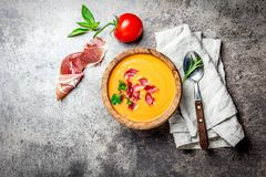 Spanish tomato soup Salmorejo served in olive wooden bowl with ham jamon serrano on stone background. Top view, copy Stock Photo