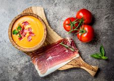 Spanish tomato soup Salmorejo served in olive wooden bowl with ham jamon serrano on stone background. Top view Royalty Free Stock Photo