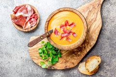Spanish tomato soup Salmorejo served in olive wooden bowl with ham jamon serrano on stone background. Top view.  royalty free stock photo