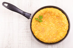 Spanish tortilla (omelette) in the frying pan Royalty Free Stock Images