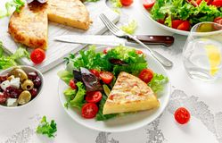 Spanish tortilla, omelette with potato, onion, vegetables, tomatoes, olives and herbs in a white plate. breakfast. Healthy food royalty free stock photos