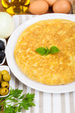 Spanish tortilla (omelette) and some ingredients Royalty Free Stock Photos