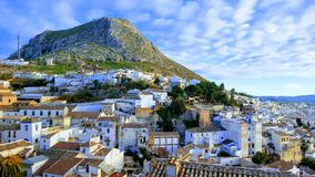 Spanish town, Martos with a mountain and white houses. Blue cloudy sky and red tiled roof Stock Photo