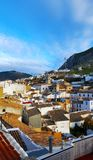 Spanish town, Martos with a mountain and white houses. Blue cloudy sky and red tiled roof Stock Photography