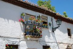Spanish townhouse with balcony, Granada. Wrought iron balcony on a traditional Spanish townhouse with assorted flowers in the Albaicin District, Granada Stock Photos