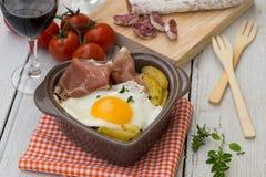 Spanish traditional dish fried eggs with serrano ham and potatoe Royalty Free Stock Photos