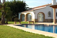 Spanish villa with pool. Spanish villa and swimming pool with grass surround royalty free stock images