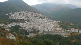 Spanish white village of Andalusia surrounded by mountains and trees. Panoramic view from above of a white city in the mountains of Spain stock video