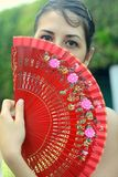 Spanish Woman. Brunette Spanish woman with brown eyes holds her fan mysteriously over her face Royalty Free Stock Images
