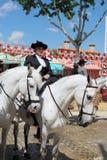 Spanish woman on a horse at the Seville Fair. Stock Photos