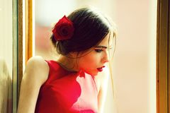 Spanish woman with makeup and red lips, rose in hair. Spanish woman with fashionable makeup and red lips, has rose flower in hair in dress at window, future and royalty free stock photography