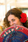 Spanish Woman with Red and Blue Fan. Spanish girl with carnations in hair and a traditional red polka dot feria dress smiles from behind her fan Royalty Free Stock Photos