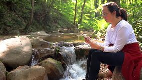 Spanish woman on the river bank with mobile phone, cinemagraph.  stock footage