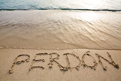 Spanish word perdón written in the sand Royalty Free Stock Images