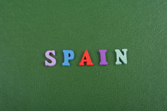 SPANJOREN uttrycker på grön bakgrund som komponeras från träbokstäver för färgrikt abc-alfabetkvarter, kopieringsutrymme för anno Royaltyfria Bilder