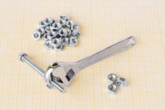 Spanner, bolt and nuts on graph paper royalty free stock image