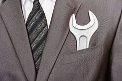 Spanner in businessman suit pocket Stock Photos