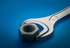 Spanner. A creative shot of spanner with nut in deep blue background Stock Photos