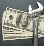 Spanner and dollars stock photography