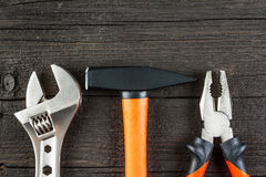 Spanner, hammer and pliers on wood Stock Photography