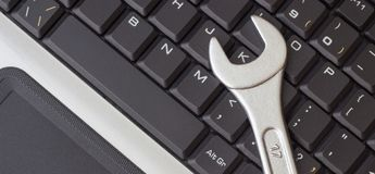Spanner on the laptop keyboard, the concept of repairing machinery, close-up stock image