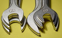 Spanner mouths. Close up of spanners on yellow background Royalty Free Stock Photos