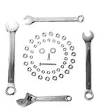 Spanner and nuts in face shape. Overhead view of spanners, nuts and screws in shape of face in frame, white background Stock Images