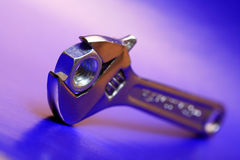 Spanner And Screw Nuts. Extreme closeup of adjustable wrench gripping a screw nut on blue and pink background Royalty Free Stock Photos