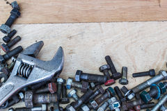 Spanner wrench and  screws on the wooden background Royalty Free Stock Photography