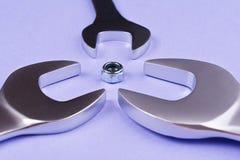 Spanners różnorodni rozmiary układali wokoło śruby na błękitnym tle Zdjęcia Royalty Free
