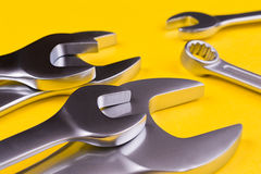 Spanners of various sizes, on yellow background. Royalty Free Stock Photos