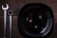 Spanners on a wooden dark background with a black plate. Table setting stock photography