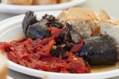 Spansk blodkorv som grillas som tjänas som med grillat röda peppar och nytt bröd Arkivfoto